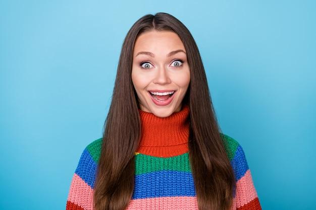 놀란 긍정적인 쾌활한 소녀의 초상화는 파란색 배경 위에 격리된 멋진 할인 비명 옷 스타일의 세련된 트렌디한 레인보우 스웨터에 깊은 인상을 받았습니다.