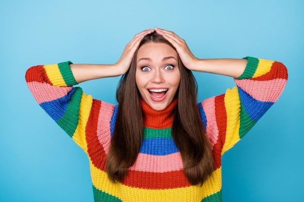 놀란 긍정적인 쾌활한 소녀의 초상화는 좋은 인상을 받은 lgbt 정보 터치 손 머리 비명 와우 와우 파란색 배경 위에 절연 무지개 스타일 점퍼를 착용