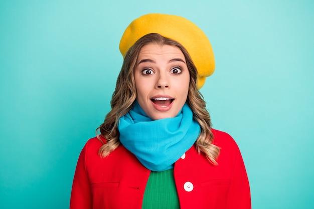 驚いたポジティブな女の子の肖像画は、冬の週末の散歩に感銘を受けた季節の販売がティール色の背景の上に分離された明るいアウターを着用しています