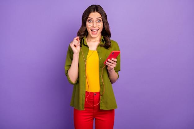 驚いたポジティブな女の子の肖像画はスマートフォンを使用して信じられないほどのラジオメロディーヘッドセットを聞いて感動悲鳴すごいomg着用スタイルスタイリッシュなトレンディなヘッドセット孤立した紫色の背景
