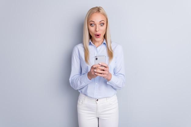 Портрет удивленной позитивной девушки, использующей смартфон, читал взволнованное лицо на серой стене