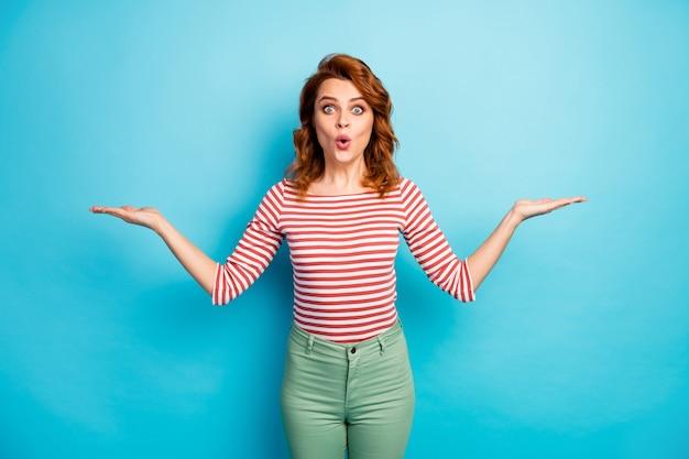 Портрет удивленной женщины, держащей руку, представляет невероятную рекламу, впечатленную криком, одетую в рубашку повседневного стиля, изолированную на синем цвете