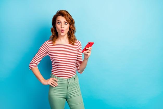 Портрет удивленной женщины, использующей смартфон, получает уведомление в социальных сетях, впечатлен крик, вау, боже, хорошо выглядит, свитер, изолированный на синем цвете