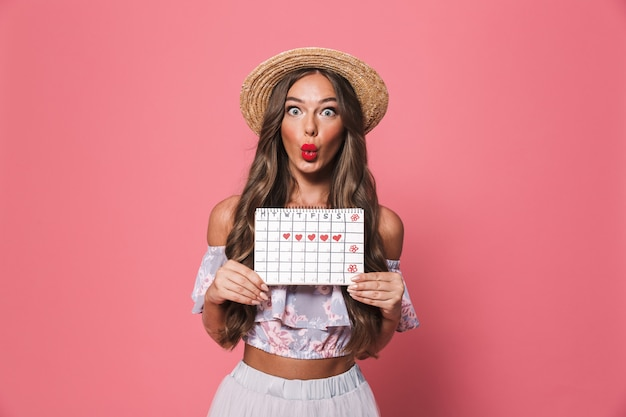 Портрет изумленной женщины нося соломенную шляпу держа календарь цикла