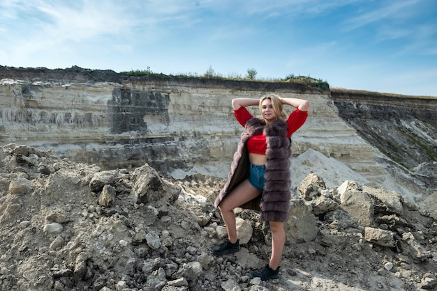乾燥した空の砂の採石場で毛皮のコートを着ている驚くべき若い女性の肖像画