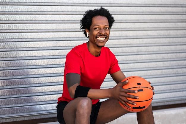 バスケットボールのボールを保持し、屋外に座ってトレーニング後にリラックスしたアスリート男性の肖像画