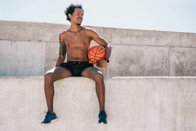 屋外に座ってバスケットボールのボールを保持しているアスリート男性の肖像画