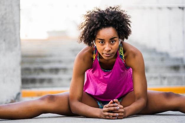 屋外で運動する前に足を伸ばすアスリート女性の肖像画。