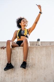 携帯電話で自分撮りをして、屋外で運動した後にリラックスするアスリート女性の肖像画。