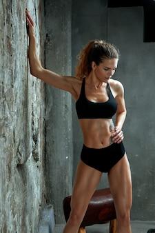 운동 백인 매력적인 맞는 여자의 초상화 돌 벽 배경에 상단과 레깅스를 입고