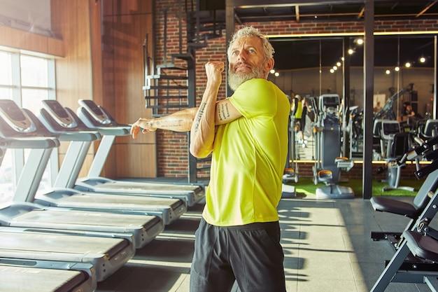 Портрет спортивного мужчины средних лет в спортивной одежде, делающего упражнения на растяжку, разогревающегося перед