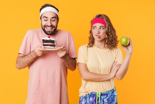 黄色の壁に分離されたbeetwenケーキとリンゴを選ぶヘッドバンドを身に着けている運動の若いカップルの肖像画