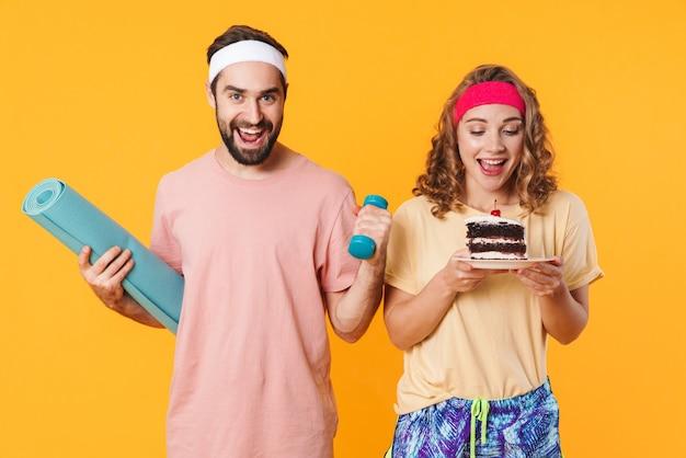 黄色の壁に隔離された不健康なケーキを保持している女性がフィットネスマットとダンベルを保持している運動の若い男の肖像画