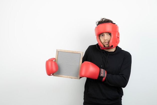 空のフレームを保持している赤いボクシング帽子の運動青年の肖像画。