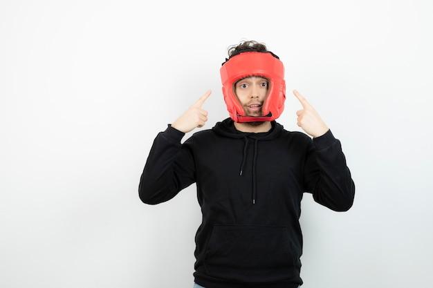 立っている赤いボクシングの帽子の運動青年の肖像画。