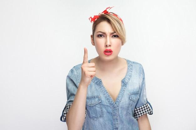 Портрет серьезной красивой молодой женщины внимания в повседневной голубой джинсовой рубашке с косметикой и красной повязкой, стоящей с предупреждением и смотрящей в камеру. крытая студия выстрел, изолированные на белом фоне.