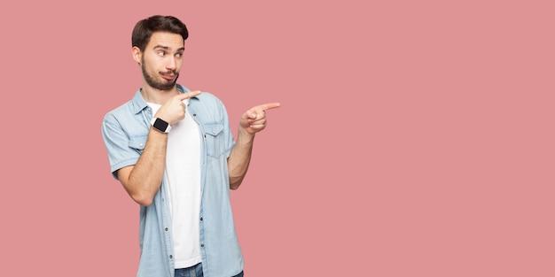 背景のコピースペースを立って、見て、指している青いカジュアルなスタイルのシャツを着た気配りのあるハンサムなひげを生やした若い男の肖像画。ピンクの背景に分離された屋内スタジオショット。