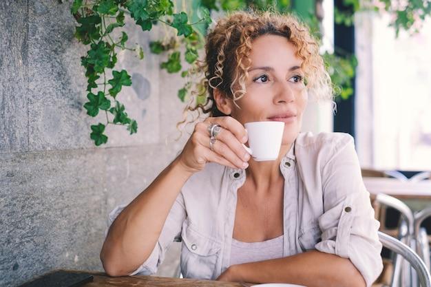 屋外のバーに座ってコーヒーを飲みながら笑顔と見ている魅力的な中年女性の肖像画。女性の大人は午後の余暇活動中にカフェで飲酒を楽しんでいます