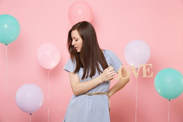 カラフルな気球とパステルピンクの背景に木製の単語の文字の愛を保持している青いドレスで目を閉じて魅力的な若い女性の肖像画。誕生日ホリデーパーティーの人々は心からの感情。