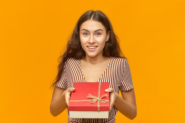 빨간색 상자를 들고 스트라이프 드레스에 매력적인 사랑스러운 젊은 유럽 여성의 초상화