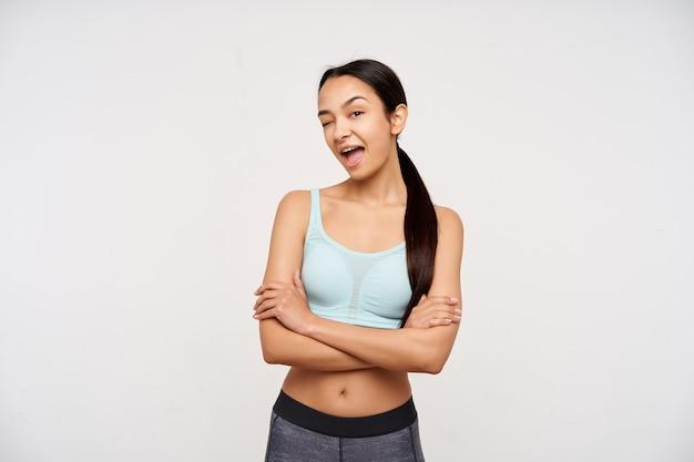 暗い長い髪の魅力的な、大人のアジアの女の子の肖像画。スポーツウェアを着て、胸に腕を組んで軽薄なウインクをします。白い背景の上に分離されたカメラで見て