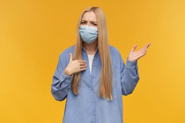 금발의 긴 머리를 가진 매력적인 성인 여자의 초상화는 혼란스럽고 그녀의 손을 올렸습니다. 파란색 셔츠와 의료용 얼굴 마스크를 착용. 오렌지 배경 위에 절연 카메라를보고