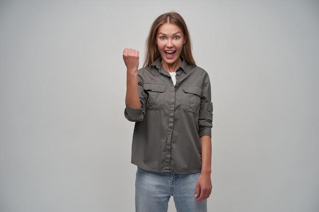 茶色の長い髪の魅力的な大人の女の子の肖像画。灰色のシャツとジーンズを着ています。拳を持ち上げたままにして、興奮と成功を示します。灰色の背景の上に分離されたカメラで見て