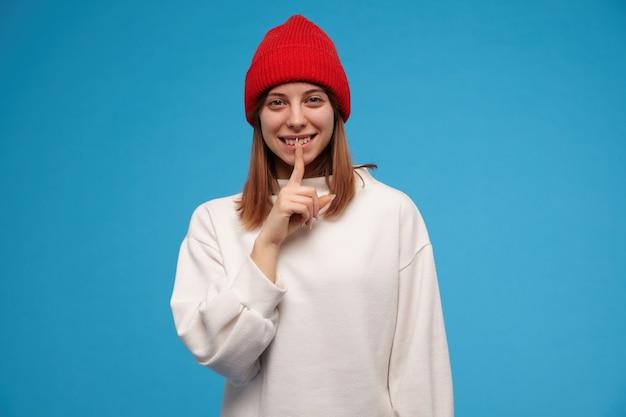 갈색 머리를 가진 매력, 성인 여자의 초상화. 흰색 스웨터와 빨간 모자를 쓰고. 침묵 기호를 표시하고 웃고. 파란색 벽 위에 절연