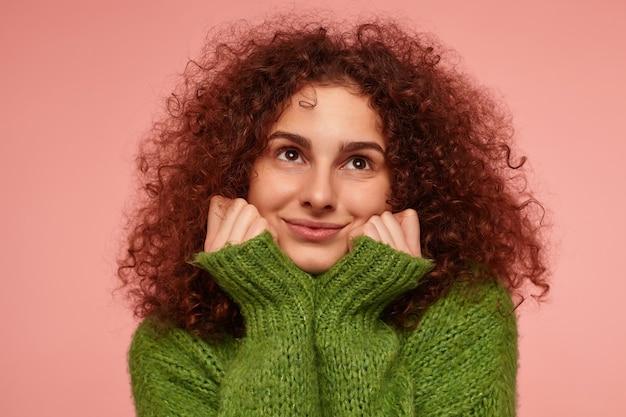 生姜巻き毛の魅力的な大人の女の子の肖像画。緑のタートルネックのセーターを着て、頬に触れて暖かく感じます。パステルピンクの壁の上の孤立したクローズアップを見ています