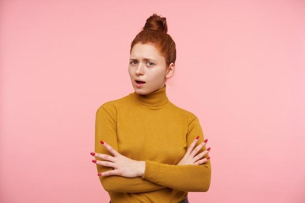 生姜髪、そばかす、パンを持つ魅力的な大人の女の子の肖像画。ゴールドのタートルネックのセーターを着て、手をつないで交差しました。パステルピンクの壁に孤立した不審なものを見ている