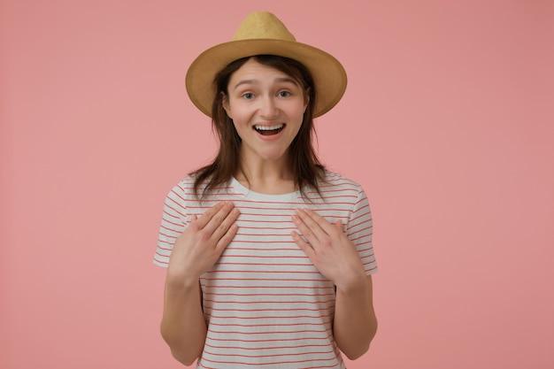 긴 갈색 머리를 가진 매력적이 고 성인 여자의 초상화. 빨간 스트립과 모자가 달린 티셔츠를 입고. 자신을 가리키고 있습니다. 감정 개념. 파스텔 핑크 벽 위에 절연