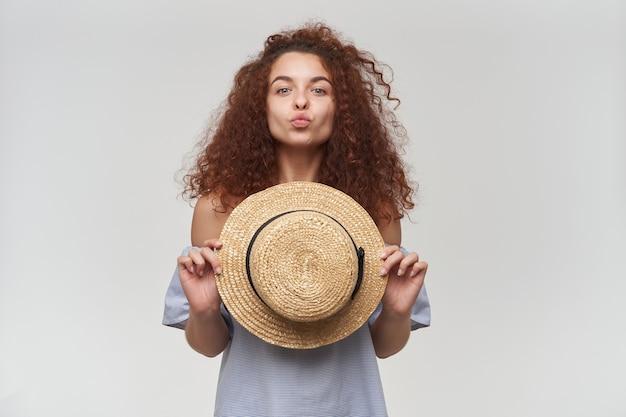 곱슬 머리를 가진 매력적이 고 성인 빨간 머리 여자의 초상화. 스트라이프 오프 숄더 블라우스를 입고 모자를 들고 있습니다. 키스하려고. 흰 벽 위에 절연