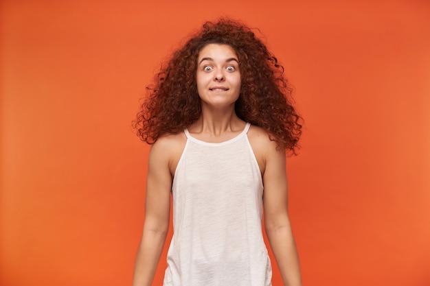 Портрет привлекательной, взрослой рыжей девушки с вьющимися волосами. надеть белую блузку с открытыми плечами. держи ее глаза широко открытыми. с нетерпением жду, изолированные на оранжевой стене