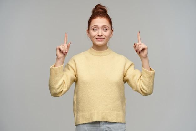 머리를 가진 매력, 성인 빨간 머리 여자의 초상화는 롤빵에 모여. 파스텔 옐로우 스웨터와 청바지를 입고. 회색 벽 위에 고립 된 복사 공간에서 가리키는