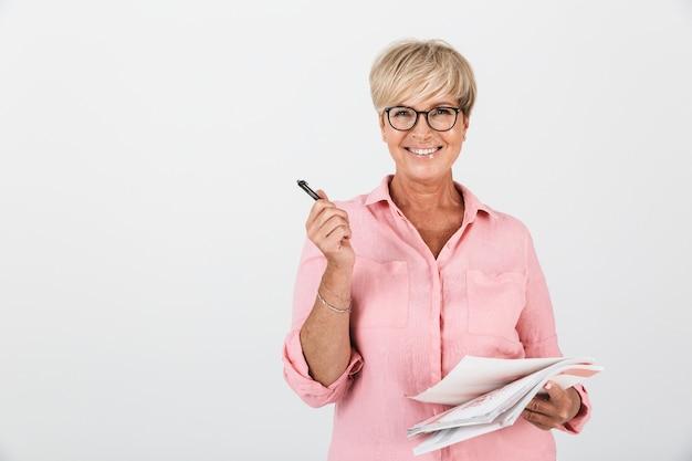Портрет привлекательной взрослой женщины в очках, держащей учебные книги и ручку, изолированную над белой стеной в студии