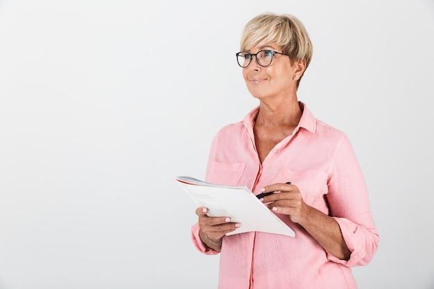 Портрет привлекательной взрослой женщины в очках, написание заметок в тетради, изолированной над белой стеной в студии