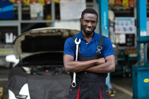매력적인 아프리카 남자 팔 십자가 모양 카메라와 큰 렌치 도구의 초상화. 자동차 수리 차고에서 일하는 전문 정비사.