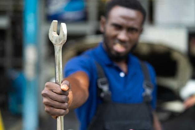 카메라와 손에 큰 렌치 도구에 웃는 매력적인 아프리카 남자의 초상화. 자동차 수리 차고에서 일하는 전문 정비사.