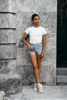 ショートパンツと灰色の壁にtショーツに魅力的なアフロアメリカンの女性の肖像画