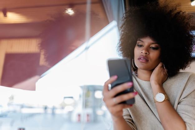 コーヒーショップで携帯電話を使用して魅力的なアフロ女性の肖像画。ビジネスウーマンコンセプト