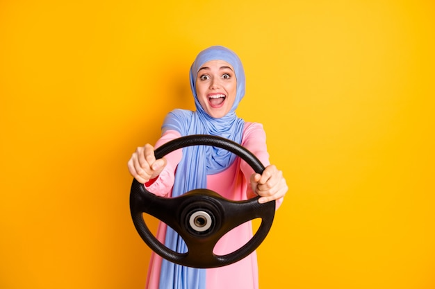 히잡을 쓴 매력적이고 쾌활한 흥분한 이슬람 여성의 초상화는 보이지 않는 차를 몰고 고립된 빛나는 노란색 배경