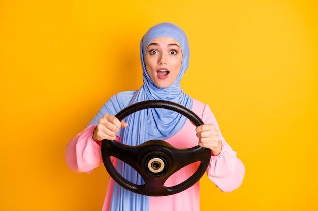 밝은 노란색 배경에서 격리된 보이지 않는 자동차 안전 여행을 하는 히잡을 쓴 매력적이고 밝고 세심한 이슬람 여성의 초상화
