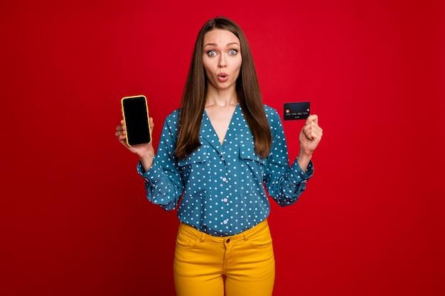 손 은행 카드 장치를 들고 있는 매력적인 놀란 소녀의 초상화는 전자 은행 입으로 분리된 밝은 빨간색 배경을 사용합니다.