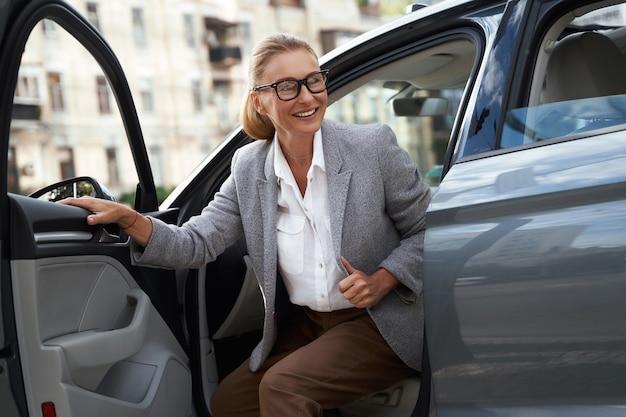 Портрет привлекательной и счастливой деловой женщины в очках, вылезающей из своего современного автомобиля