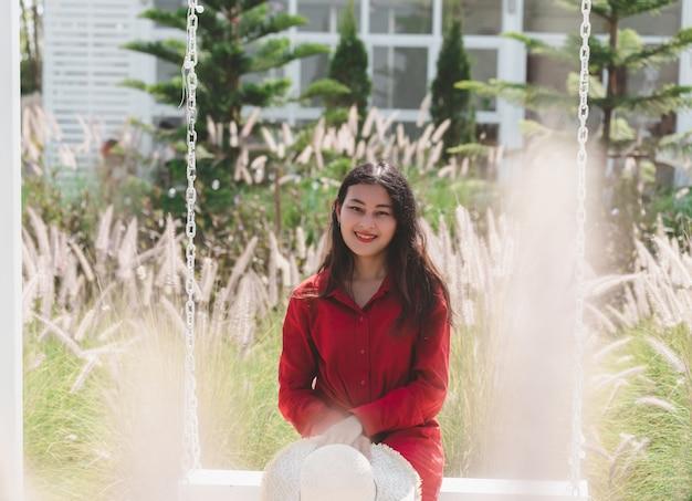 Портрет привлекательной азиатской женщины в красном платье расслабиться, сидя на качелях в цветочном саду из белого стекла