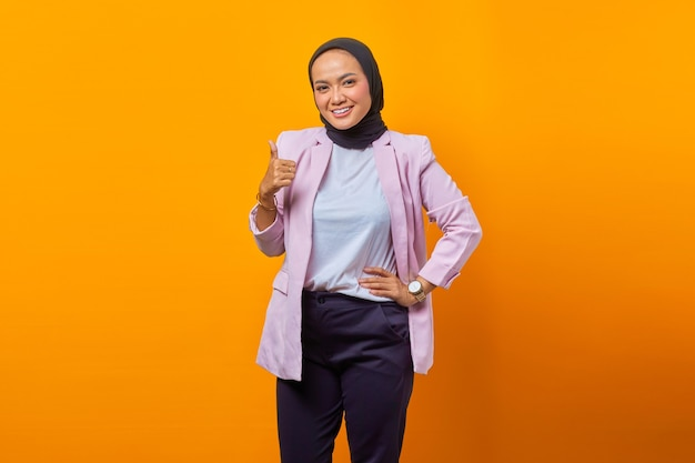 노란색 배경 위에 엄지손가락을 치켜들고 웃고 있는 매력적인 아시아 여성의 초상화