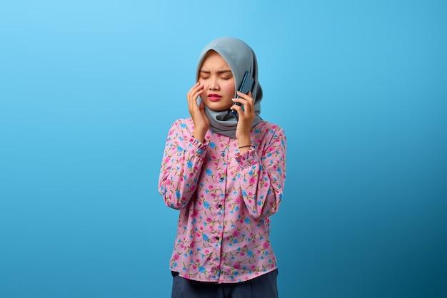 스마트폰으로 이야기하고 우는 것을 보고 있는 매력적인 아시아 여성의 초상화