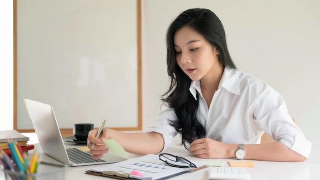 Портрет привлекательной азиатской молодой женщины предпринимателя дела работая на современном офисе