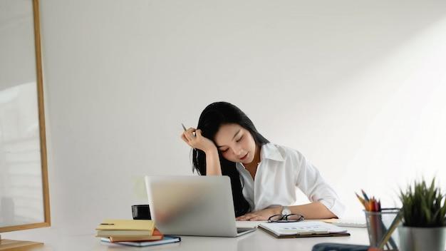 Портрет привлекательной азиатской молодой женщины предпринимателя дела работая для плана маркетинга на современном офисе