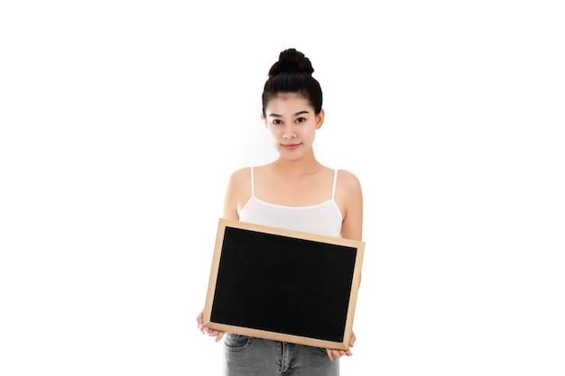 美肌と空の黒板を保持している顔を持つ魅力的なアジアの若い女性の肖像画。